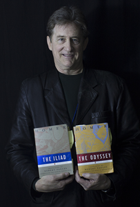 Professor Raymond Healey holding books The Iliad and The Odyssey.